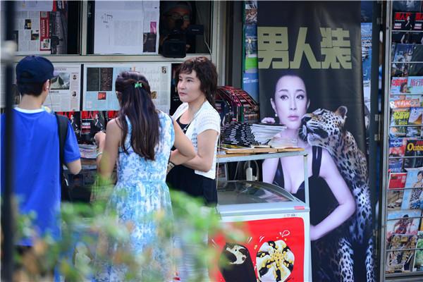 晓庆变身报刊亭老板娘,而报刊亭边上正大大的挂着她拍摄的杂志照片
