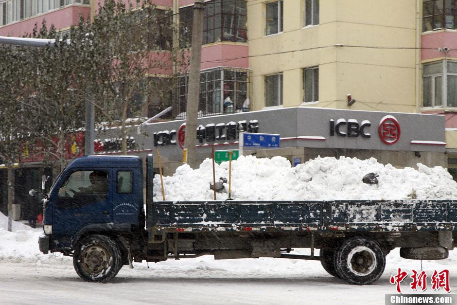 积雪严重,一些道路出现严重的堵车,城管部门的清雪车辆和人员图片