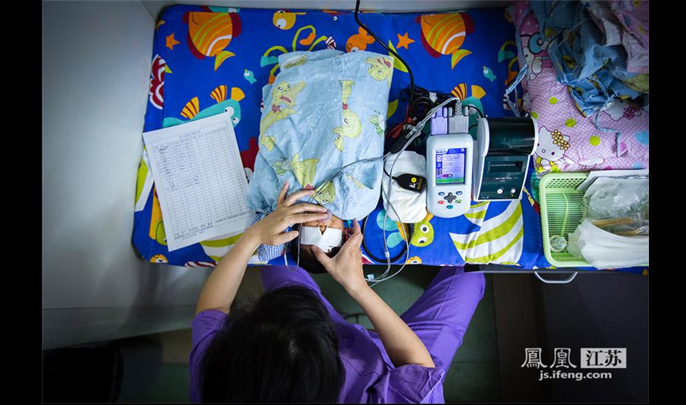 护士在给早产儿做听力测试。据介绍,听觉系统是婴儿最先发育成熟的器官,护士们常常在暖箱里放音乐给早产儿听,这样能够刺激早产儿听力系统的发育。(林琨/摄 胥大伟/文)