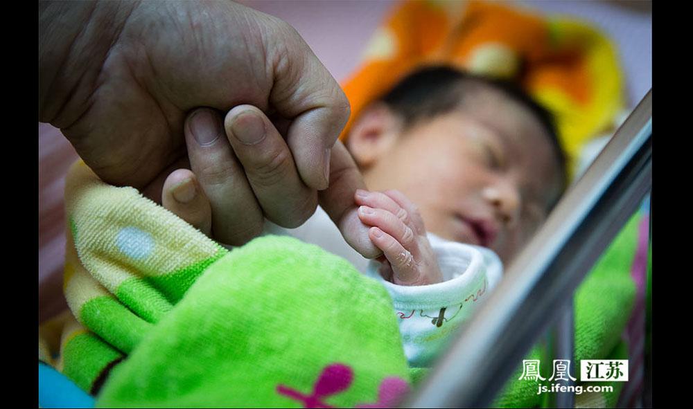 """阚玉龙伸出手指让孩子握住。今年40岁阚玉龙来自吉林,目前住在南京,是位自由职业者。他说这次生二胎夫妻俩事先并没有准备,""""既然有了就要了""""。他说父亲节自己的愿望就是""""希望孩子平安,祝愿天下父母身体健康,阖家欢乐。""""(林琨/摄 胥大伟/文)"""