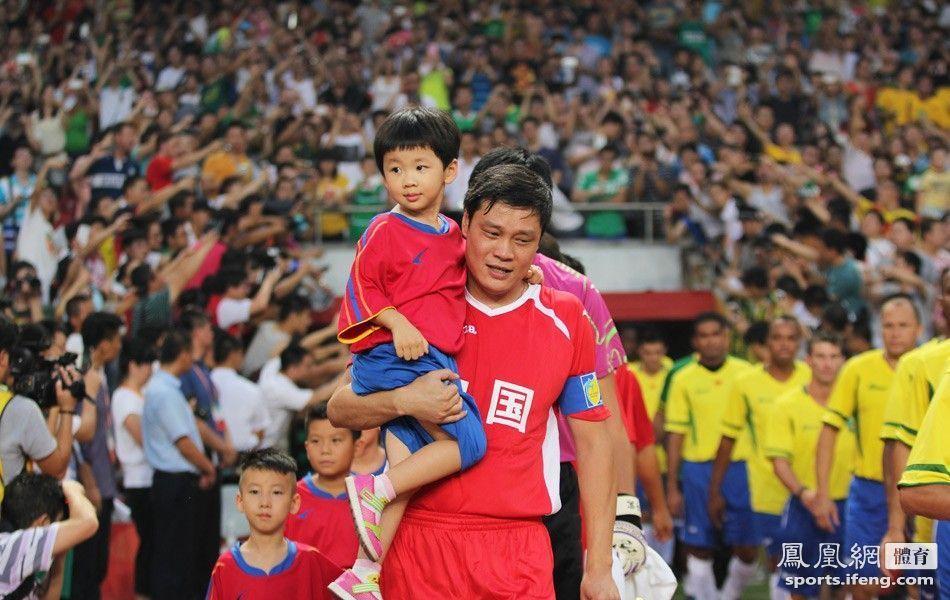 范志毅抱着球童出场. 凤凰体育/任文凯 摄-中巴元老对抗赛 巴西明星图片
