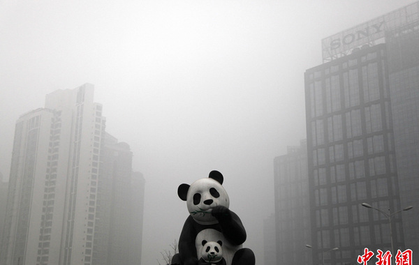 2月28日,当日北京的天空再次被雾霾笼罩,全城多地空气质量达到严重污染级别。图为熊猫雕塑被大雾笼罩。中新社发 韩海丹 摄…