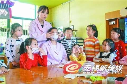 幼儿园的保健老师,在给小朋友讲述科学戴口罩的知识