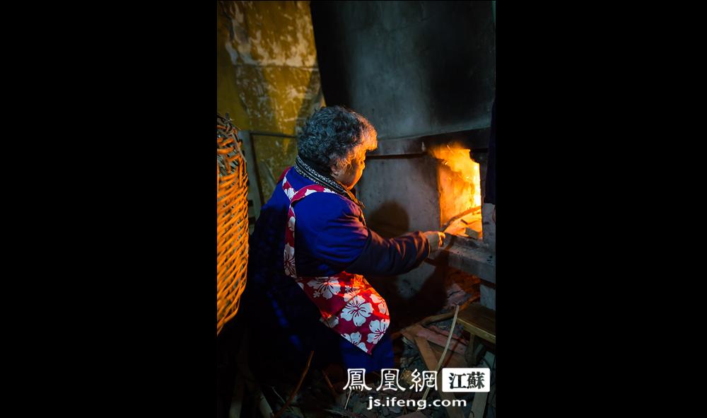 """礼毕,严师傅大喊一声""""点火"""",73岁的朱大妈便将灶膛的火烧得熊熊。柴火是从附近拆迁工地搬来的木料。灶君王的旧对联也要放进灶膛里烧掉,化成烟灰,严师傅说这是灶君王上天""""言好事""""去了。(黄埔7号影像俱乐部/图 胥大伟/文)"""