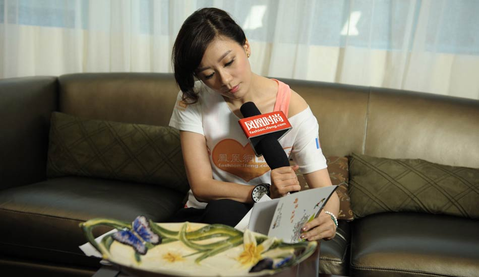 贾静雯接受凤凰时尚独家专访并认真翻看图书