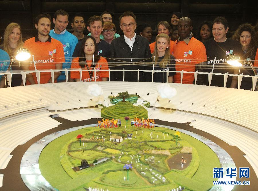 6月12日,伦敦奥运会开幕式导演博伊尔(中)与志愿者和工作人员在开幕式现场模型前合影。当日距离伦敦奥运会开幕还有45天,博伊尔慰问并感谢了10000名参与开幕式准备工作的志愿者和工作人员。