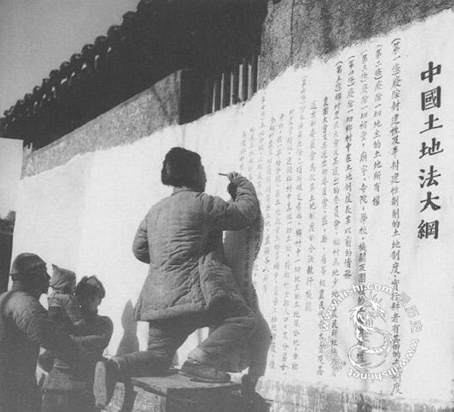 """1947年10月10日,中共中央正式公布《中国土地法大纲》:""""废除封建性及半封建性剥削的土地制度,实行耕者有其田的土地制度;乡村中一切地主的土地及公地,由乡村农会接收,连同乡村中其他一切土地,按乡村全部人口,不分男女老幼,统一平均分配;乡村农会接收地主的牲畜、农具、房屋、粮食及其他财产,并征收富农的上述财产的多余部分,分给缺乏这些财产的农民及其他贫民,并分给地主同样的一份。""""图为河北阜平县易家庄的农民在墙上书写《土地法大纲》。"""