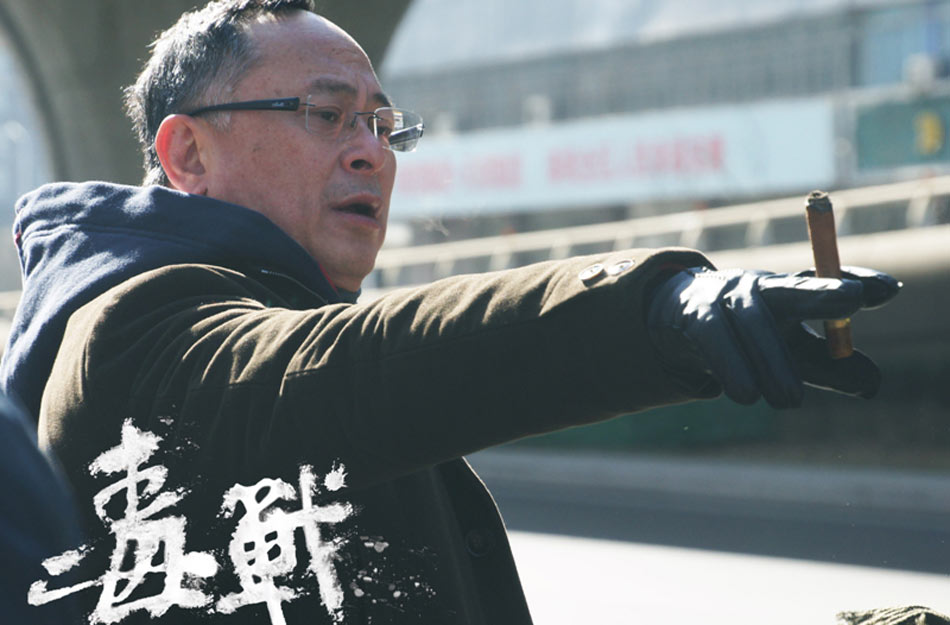 """。日前,《毒战》曝光了一组杜琪峰的片场照,以及他的""""警匪片25周年""""视频特辑。图为《毒战》片场照,杜琪峰现场指导。"""