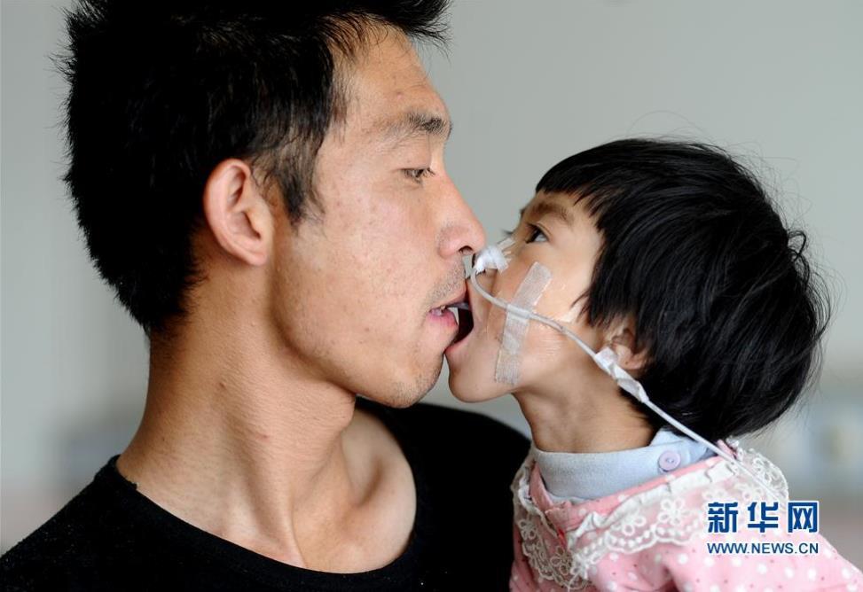 高清图—山西左权县泽城村喂食爸爸王志华嘴对嘴喂食女儿