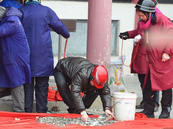 香客祈福扔硬币 工作人员戴头盔清理