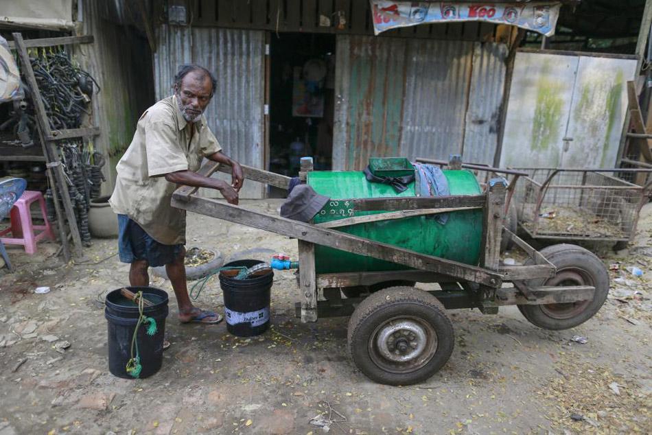 一位居民用旧油桶做成的水车运水