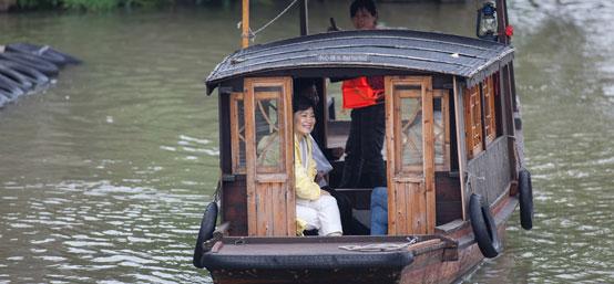 林青霞冒雨游乌镇 一袭黄衣船上赏景