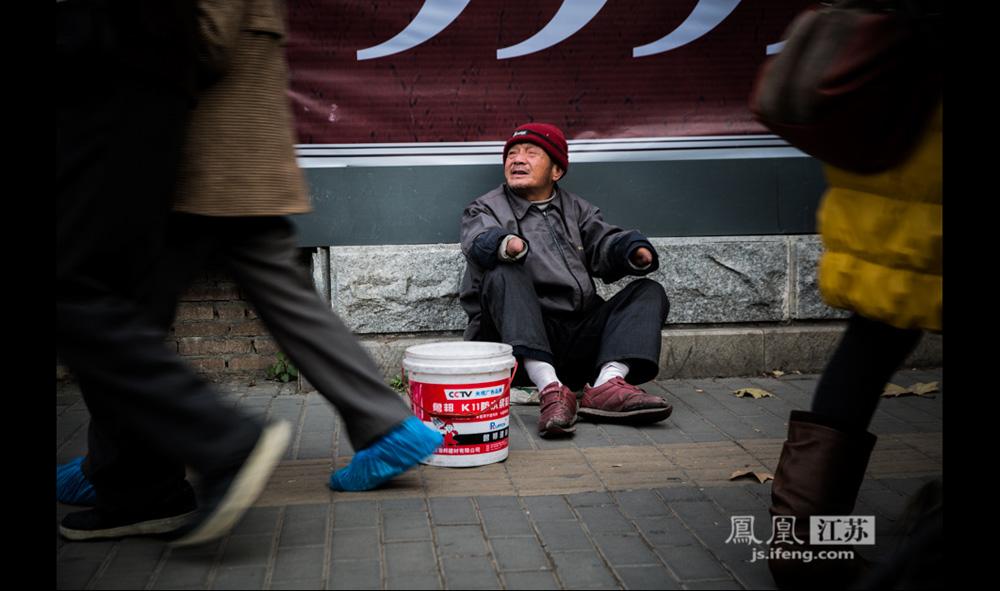 12月9日,南京一家医院门口,这位64岁的男子坐在墙根举着光秃秃的手臂向行人讨钱。他说自己是安徽岳池县人,二十多年前在家自制鞭炮时,因一次爆炸事故失去双手,妻子丧生。他有一个儿子四十多岁,因为与儿媳妇关系不和,所以男子带着八十多岁的母亲来南京乞讨,已经十几年。(彭铭/摄 孙子玉/文)