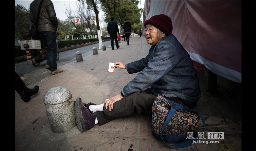 老人今年84岁,12月9日,她坐在某地铁站附近,举着纸杯向过往行人要钱。她是前一张图片中男子的母亲,两人在南京街头分开乞讨,但不会离开太远,因为要给儿子喂饭。(彭铭/摄 孙子玉/文)
