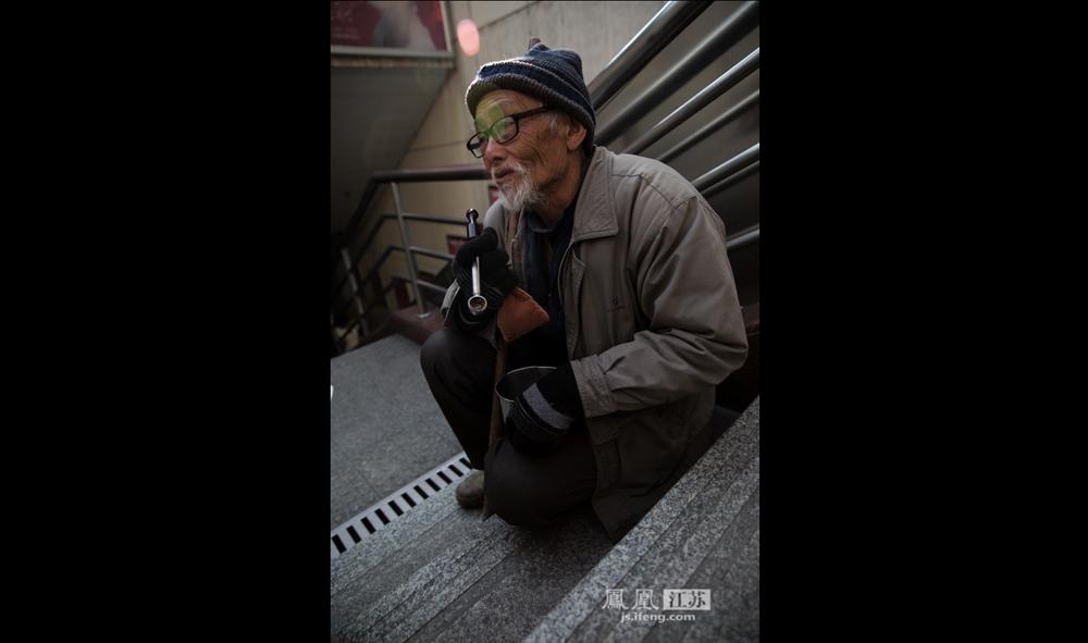 """12月9日,南京人流汹涌的新街口地铁站,这位80岁的老人坐在台阶上抽烟斗。他说他来南京乞讨已有两年,一天能要二三十块钱。他说儿子出车祸去世,儿媳改嫁,留下四个孩子,最大的18岁在打工,其余三个在上学,现在安徽老家,由老伴照顾。他说:""""农忙时我回家帮忙,闲的时候就出来乞讨。""""(彭铭/摄 孙子玉/文)"""