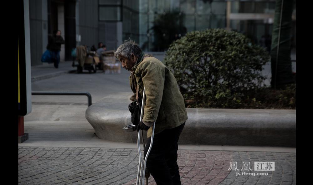 12月9日,南京新街口,63岁的老人拄拐走在街头。他称自己以前在西藏批发水果,5年前腿受伤,就医时又发生医疗事故,两年没能起床,出来乞讨已三年,去过东北、上海、南京等好多地方。他老婆去世6年,女儿现在山西上大学,儿子在西藏上高中,两个孩子都靠自己要饭供着。(彭铭/摄 孙子玉/文)
