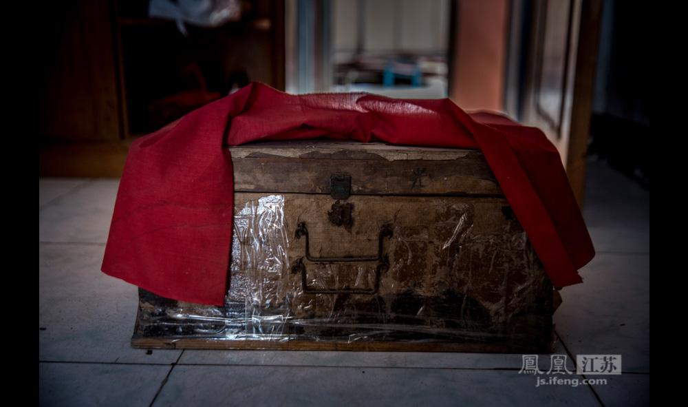 """每年清明和冬至,郑家村都会举行隆重的祭祀仪式,在村中各户人家轮流举行,纪念郑和,缅怀先人。今年的祭祀,正好轮到郑贵祥家。4月5日清明这天一大早,郑贵祥从去年举行仪式的人家取来这个古旧厚重的木箱,里面装的是郑氏宗谱。郑贵祥的妻子说:""""几百年了,箱子不知已经换了多少个了。""""(彭铭/图 孙子玉/文)"""