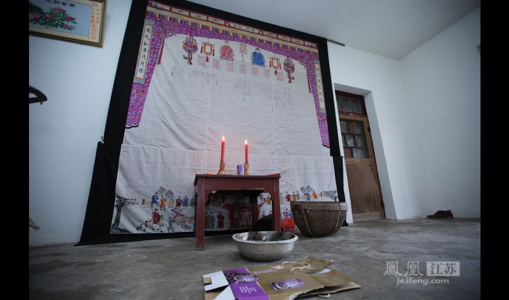 """郑氏宗谱。约12平方米的布制宗谱,满满挂了郑贵祥家的一面墙。不过,""""这并不是原来的,原来的族谱写满了祖先的名字,而且比现在这个大许多,但在文革时期遭到焚毁。现在的族谱是80年代凭记忆重新制作的。""""(彭铭/图 孙子玉/文)"""