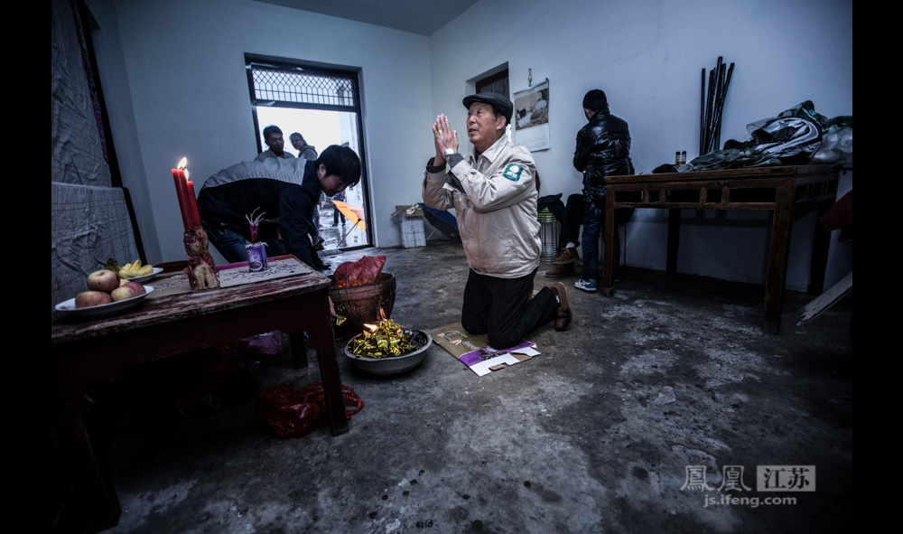 """68岁的郑善雪老人在族谱前磕头叩拜。他家搬到周村已经30多年,不过每年的祭祀仪式他都会来:""""这是我们的祖宗,不来怎么行""""。改革开放后,小小的郑家村难以容纳数百名村民,因此曾有十多户人家迁居到马路对面的周村。(彭铭/图 孙子玉/文)"""