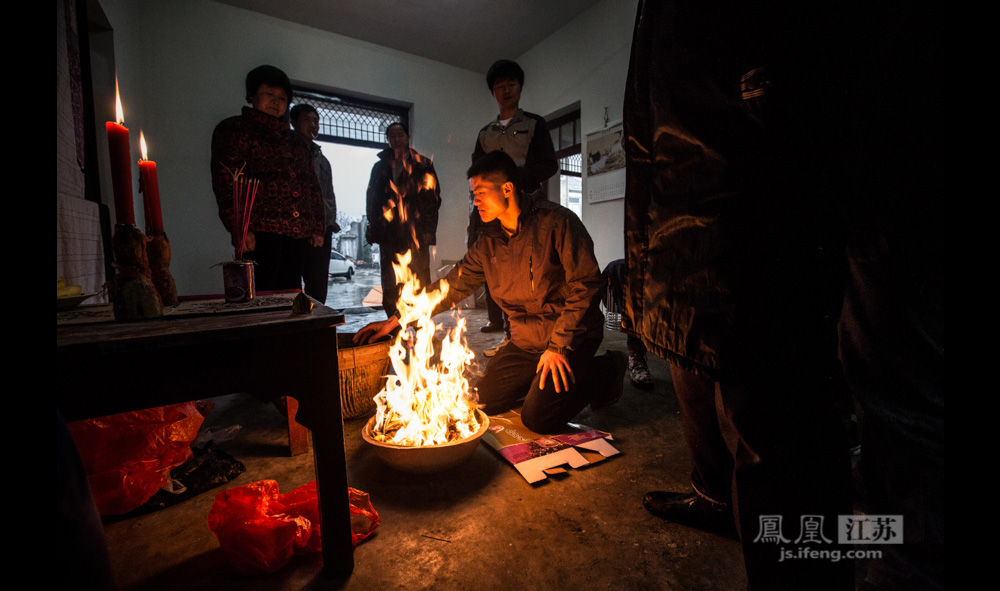 郑贵祥的二儿子在族谱前烧纸、叩拜。(彭铭/图 孙子玉/文)