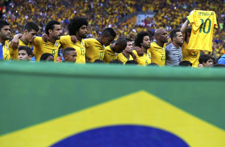 2014年7月9日,巴西米内罗竞技场,2014巴西世界杯半决赛,巴西vs德国。队友祝福内马尔,大卫-路易斯举其球衣唱国歌。