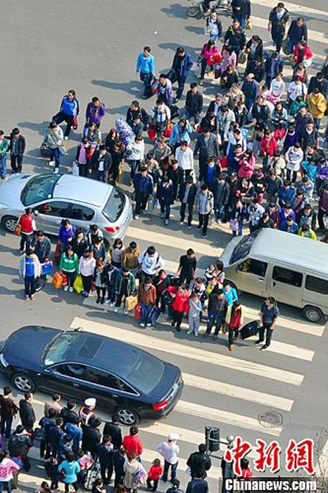 近日,中国有网友发微博称,中国式过马路,凑一撮就走,和红绿灯无关,对部分中国人集体闯红灯现象调侃,引发各方民众热议。图为山西太原火车站附近的行人无视红绿灯穿越马路。中新社发 韦亮 摄
