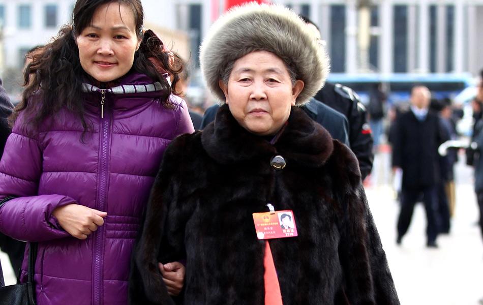 """3月12日,正在北京举行的十一届全国人大五次会议上,中国著名辣椒制品品牌创始人""""老干妈""""陶华碧表示:""""'老干妈'3年缴税8个亿,实现31亿元人民币的产值,带动两百万农民的致富,我还是按照我的知识来办事。""""65岁的陶华碧只有小学文化程度,从摆地摊起家,历经艰辛,成为中国最大辣椒酱企业的掌门人。图为行事低调的陶华碧代表(右)赴会。泱波/摄"""