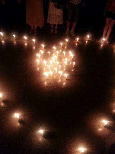 """蜡烛摆放成的内含""""安""""字样的心形面前"""