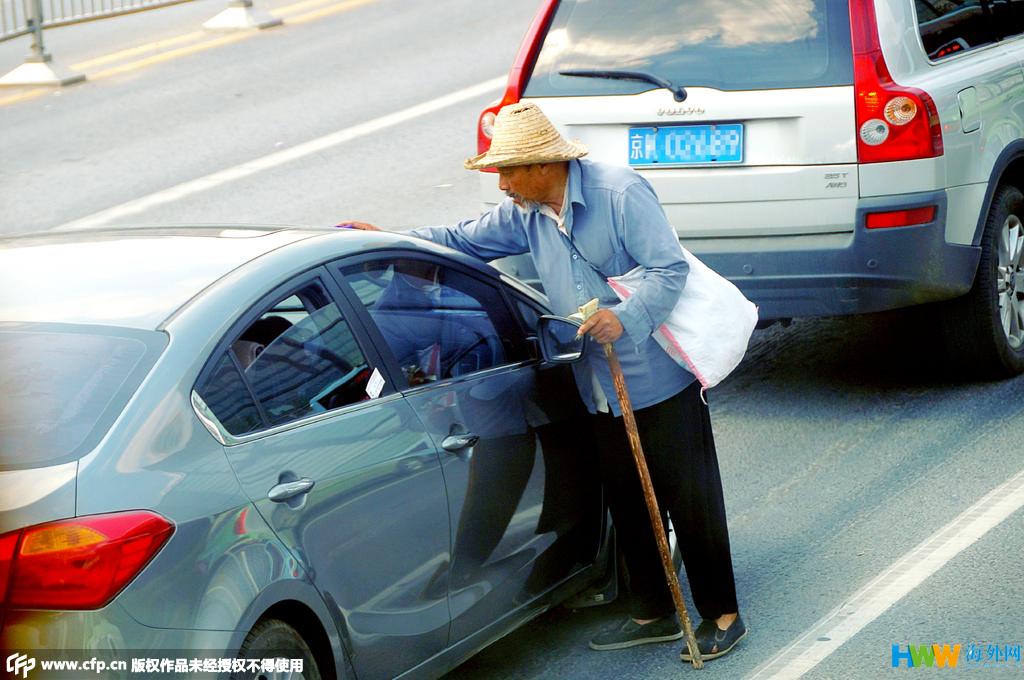 后敲车窗示意车主给钱. 图为老汉抹一抹一辆汽车的前挡风玻高清图片