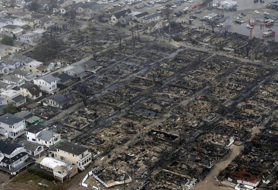 """超级风暴""""桑迪""""自美国东部时间29日晚强势登陆新泽西州南部沿岸以来,至30日上午已重创人口稠密的美国东海岸地区,导致至少16人死亡。美国第一大城市纽约是此次风暴中受灾最严重的地区之一。其中,有着上百年历史的地铁系统设施遭到洪水严重破坏,连接布鲁克林和曼哈顿的10条隧道也全部遭洪水淹浸。此外,洪水也涌入处于低洼地带的曼哈顿下城,淹没大片街道,当地居民被下令撤离。美国第一大城市纽约是此次风暴中受灾最严重的地区之一。图为皇后区发生的一场火灾,该火灾由飓风引发的洪水导致。"""