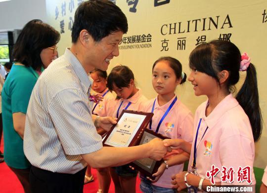 上海 瞿国樑/上海市台办副主任瞿国樑向获奖小学生颁奖。潘索菲摄