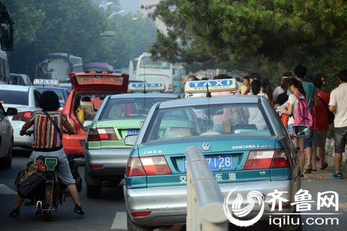 7月27日,青岛海底世界门前,多辆出租车随便停在路边拉客。(本网记者 摄)