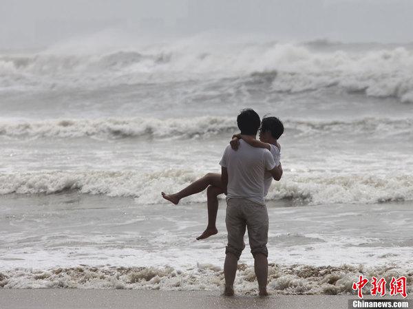 台风百合三亚掀巨浪 情侣海滩相拥
