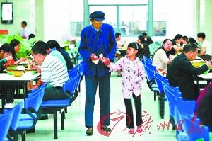 一老一少两名昆明市民,就餐结束后离开机关食堂。图片来源:都市时报