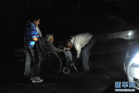"""当地时间4月1日,在智利伊基克,地震后人们帮助一名坐轮椅的老人撤离。图片来源:新华网src=""""http://y2.ifengimg.com/cmpp/2014/04/02/18/2f16eb48-4805-4721-95a2-0ba3bd75928d.jpg"""""""