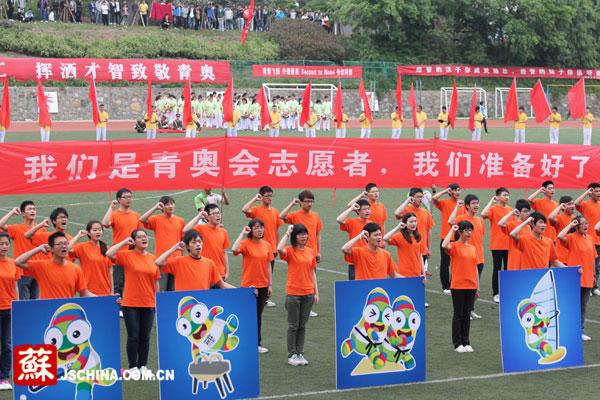运动场上,大学生志愿者手握拳头,高声宣誓.