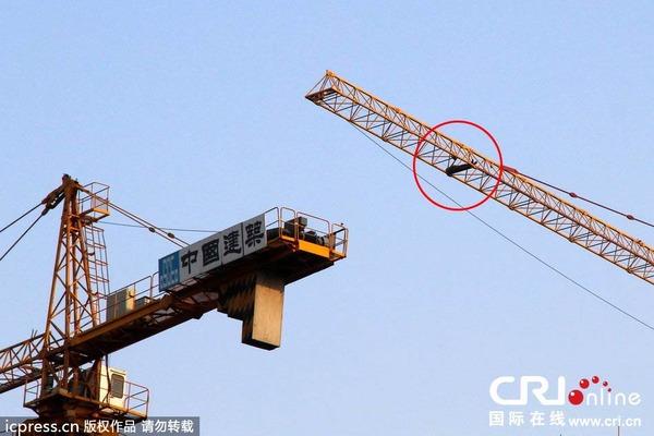 4月30日傍晚,塔吊男仍在高空休息。图片来源:东方IC 2014年4月30日傍晚,北京市西城区珠朝街附近的一处工地,塔吊男仍在高空休息。 4月21日,一名男子进入北京市西城区珠朝街附近的一处工地,并爬上了该工地的塔吊。到目前为止,该男子已经在几十米高的塔吊上停留了9天。 根据现场救援人员介绍,该男子来自浙江,自4月21日以来,包括警察、消防、工地安保人员及其家人等在内的救援人员,多次尝试对其进行施救,但该男子一直拒绝配合,其家人也只好将食物等必需品通过塔吊传送设备投送给该男子。救援人员已在