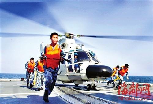 24日,航空兵地勤人员在为舰载直升机起飞做机务准备