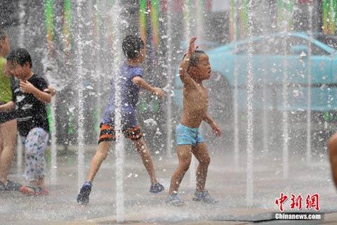 7月20日,北京天气炎热,孩子们在喷泉中嬉水纳凉。