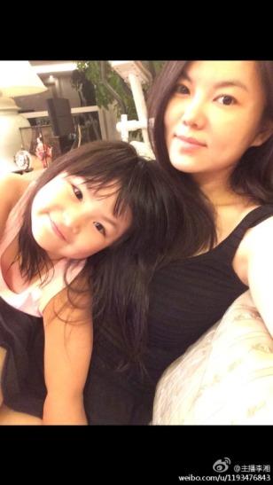 的合影.照片中,李湘素颜坐在沙发上,王诗龄则在妈妈怀里摆出