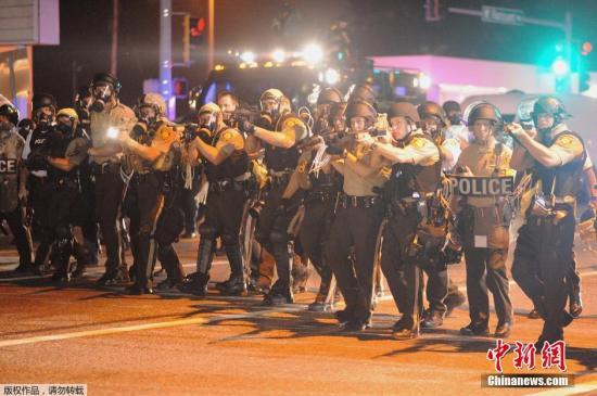 当地时间8月18日,全副武装的执法人员在弗格森市维护治安。