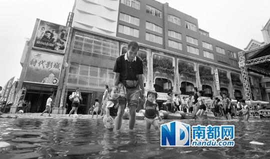 2013年8月,佛山创意产业园内一名大人带着两个小孩在园内临时搭建的滨海沙滩玩耍。