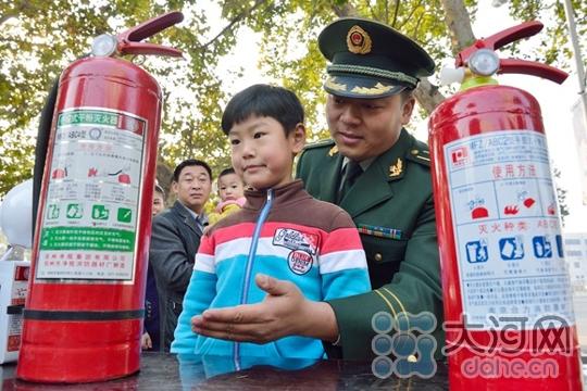 消防武警在教孩子们如何使用灭火器消防武警在为孩子们普及消防知识
