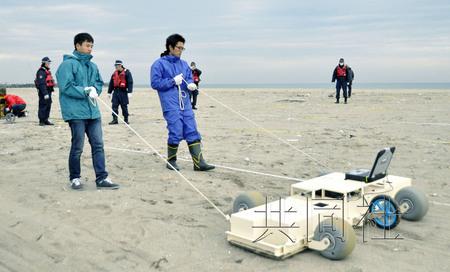 日本警方在沿岸寻找失踪者线索.(来源:共同社)-东日本地震3年9
