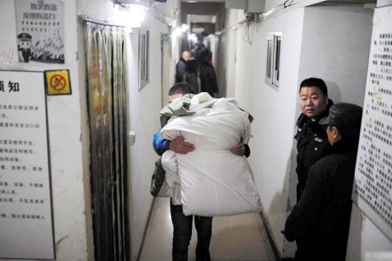 北京消息 北京石景山区衙门口村一处二层楼下,掩藏着一个偌大的地下室,深约4米,面积约2400平方米,共建成170多间隔断房出租给住户。据相关部门称,已确定地下室属于违建。1月31日零时,地下室的清理工作仍在进行中。目前,有37户租户被安置到附近周转房。 石景山衙门口村是京西最大的城中村之一,1月30日深夜,村东的一个汽修大院里仍人头攒动,不断有人抱着被褥从地下钻出来(见左图)。 私挖地下室的韩广明称,他与合伙人从赵国强手中承包废弃鱼塘,每年租金40万元。随后出资212万元,2013年5月开始施工,建造