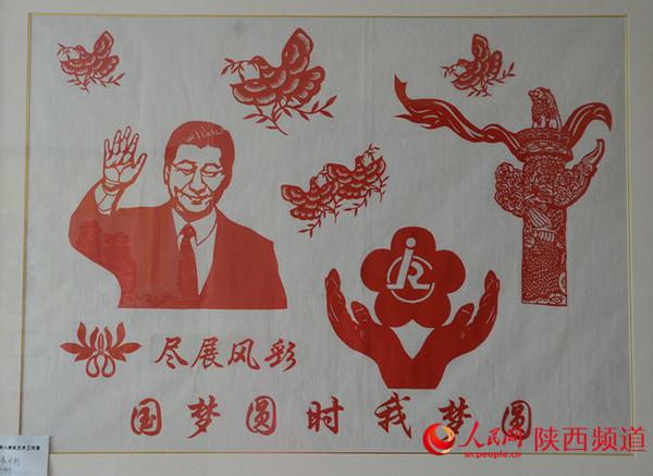 《尽展风彩 国梦圆时我梦圆》刘惠霞作品。展示新一代国家领导人的风采,歌颂团结祥和的社会风气。合手托起的残疾人徽标,预示着全社会对残疾人的关爱、关注和关怀;整体画面显出尽展风彩,国梦圆时我梦圆的美好夙愿。 和冰/摄 前言:刘慧霞,人称白鹿霞子,非物质文化遗产剪纸传承人。祖籍陕西关中腹地白鹿原,襁褓中随父母迁居西安莲湖区,醉心于剪纸艺术,其作品被认为杂糅汉代石刻写意手法,线条舒展、形态优雅。她的剪纸技艺在保留传统民俗剪纸原生态的基础上形成自己独立的艺术风格。她在西安市莲湖区残联兴办剪纸艺术工作室,倾囊相授