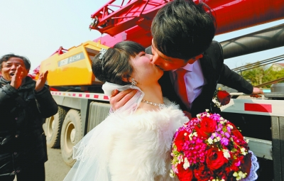 新郎和新娘在吊车前甜蜜相吻。