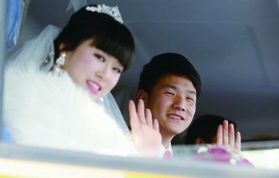 新郎和新娘坐在驾驶室里一脸幸福。