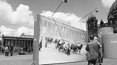 """5月1日,在德国柏林博物馆岛广场,一名怀抱婴儿的男子观看""""战争与和平间的日常生活""""露天图片展。 为期一个多月的露天图片展再现战时场景,教育人们铭记历史。"""
