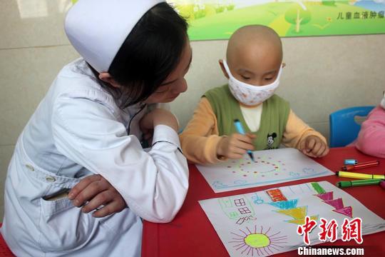 图为白血病小朋友在医院护士老师的帮助下开心的绘画